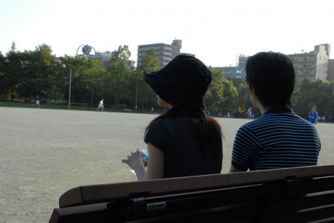 ベンチで会話するカップル