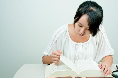 辞書を調べる女性
