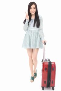旅行かばんを持つ美女