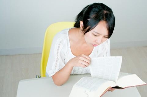 辞書を手に取る女性