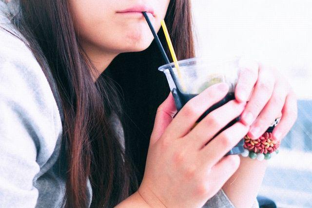 デート中に飲み物をストローでチューチューする女性