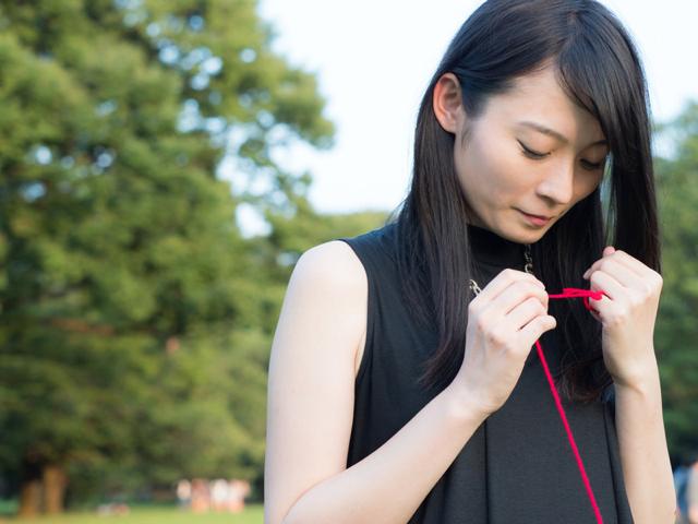 赤い糸を手繰り寄せる女性